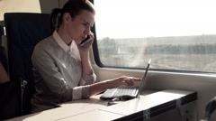 Businesswoman talking on cellphone, working on laptop, in train HD Stock Footage