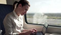 Young businesswoman working on laptop during train ride HD Stock Footage