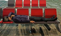 weary traveller napping due to jet lag - stock photo