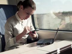Businesswoman writing notes on smartphone with stylus pen on a train NTSC Stock Footage