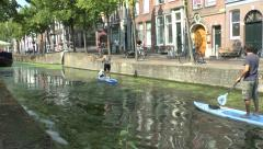 Paddle boarding (surfing) along the canal in Delft, South Holland, Netherlands. Stock Footage