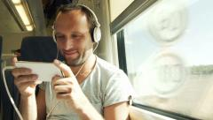 Happy man playing funny game on his smartphone during train travel HD Stock Footage