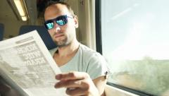 Young, handsome man reading magazine on a train HD Stock Footage