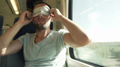 Young man with sleeping eye mask on a train HD Stock Footage
