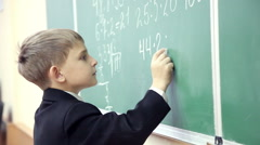 Little boy solves math on the blackboard at school 6 Stock Footage
