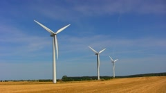 Three wind turbines on a stubble field Stock Footage