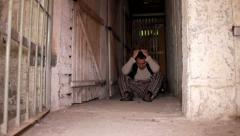 Man sitting on the cellar ground when cell door open Stock Footage