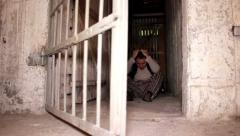 Man sitting on the cellar ground when cell door open - astonishment Stock Footage