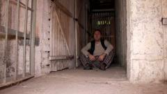 Man sitting on the cellar ground when cell door open - happy freedom Stock Footage