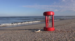 Ancient red broken hourglass sandglass clock on sea beach sand Stock Footage