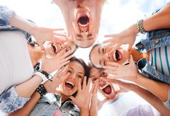 group of teenagers looking down and screaming - stock photo
