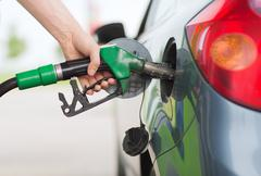 Man pumping gasoline fuel in car at gas station Stock Photos