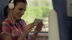 Young woman watching funny movie on her smartphone on a train  HD Stock Footage