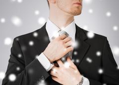 man adjusting his tie - stock photo