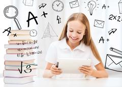 girl with tablet pc and books at school - stock photo