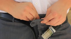 Man fastening belt on his trousers Stock Footage