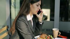 Businesswoman talking on cellphone outside the cafe and looking papers, steady Stock Footage