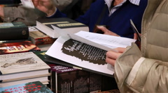 Buyers considering the book at the book fair. - stock footage