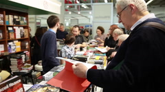 Buyers considering the book at the book fair. Stock Footage