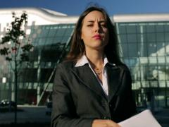 Businesswoman walking with papers and doing serious look to the camera, steady Stock Footage
