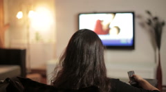 Dolly shot of a woman watching tv in living room - stock footage