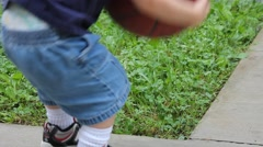 Toddler bounces ball on front porch Stock Footage