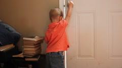 Toddler opening up front door Stock Footage