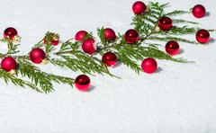 Stock Photo of evergreen bough with red ornaments
