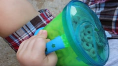 Close-up of a toddler's hand holding a snack cup - stock footage
