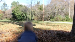 Toddler Playing with Leaves Outside Stock Footage