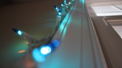 Christmas lights strung up on a window frame Stock Footage