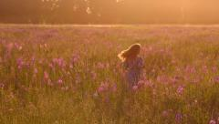 Beautiful girl runs in the field of flowers at sunset - stock footage