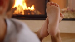 Little boy lying in front of the fireplace, cute toes Stock Footage