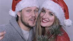 Happy beautiful Christmas couple singing carols over white background.  Stock Footage