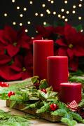 red candle centerpiece with greens and holly - stock photo