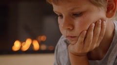 Little boy draws a picture in front of the fireplace, face - stock footage