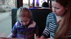 Young girl with mother choosing food menu in restaurant Arkistovideo