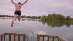 Two guys run and jump into the water Stock Footage