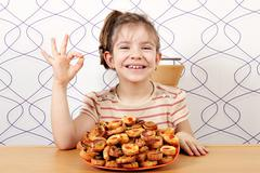 Happy little girl with bruschetti and ok hand sign Stock Photos