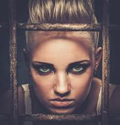 Troubled teenager girl behind bars Stock Photos