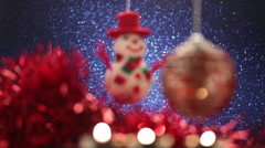 Christmas ball and snowman on glitter blue background. Rack focus Stock Footage