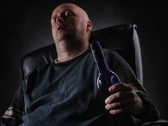 Sleeping middle aged alcoholic and wine bottle Stock Photos