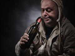 Stock Photo of middle aged alcoholic and wine bottle