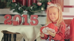 Little blond girl with long hair and wearing a red sweater with snowmens shakes Stock Footage