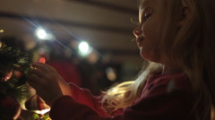Cute little girl decorates Christmas tree for the New Year Stock Footage