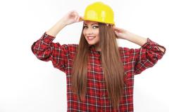 young female architect or builder wearing a yellow hart hat on a construction - stock photo