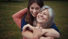 Daughter surprises mother with a loving hug from behind - stock footage
