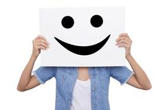 Girl holding a placard with a smiling smiles front of her face - stock photo