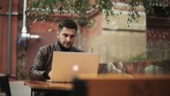 A man uses a laptop outdoor. Footage with slider Stock Footage