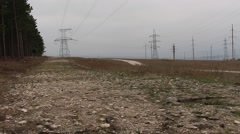 High-voltage lines, forest and rural road in the prairie - stock footage